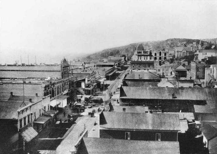 Then: Looking north from Pioneer Place (square) into the uptown of what was easily the largest town in Washington Territory. This is judged by the 3218 votes cast in the November election of 1884, about one fourth of them by the newly but temporarily enfranchised women.Tacoma, in spite of being then into its second year as the terminus for the transcontinental Northern Pacific Railroad, cast 1663 votes, which took third place behind Walla Walla's 1950 registered votes.
