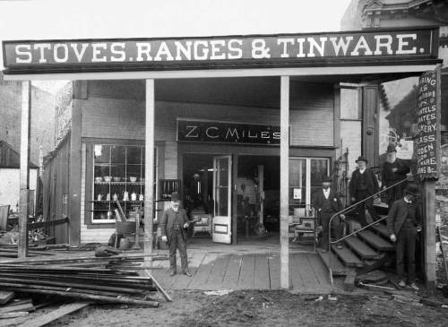 THEN: For the first twenty years of his more than 40 years selling tinware and other selected hardware, Zilba Mile's shop looked south across Yesler Way down First Ave. S, then known as Commercial Street.