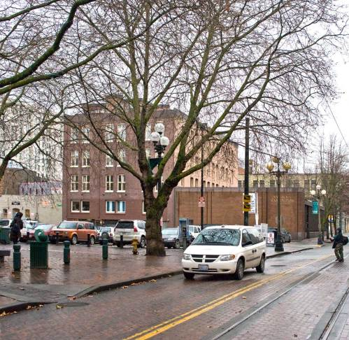 NOW: Jean Sherrard moved in a few feet closer to the northeast corner of Main and Occidental to better show the cars parked where once the landmark hotel sat and also the stylish posts that have closed Occidental between Main and Washington since neighborhood architects Jones and Jones developed Occidental Park for the city in the early 1970s.