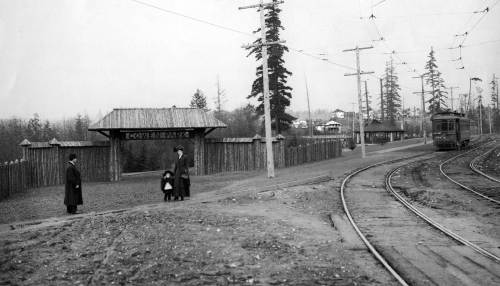 In 1909 the Eastlake Trolley up University Way reached the end of its line along the southern rim of Ravenna Park.  Where it turned towards 15th Avenue. N.E. it passed the rustic gate to the nearly new Cowen Park at Ravenna Boulevard.   The line of the original 15th Avenue pedestrian bridge across the ravine can be followed – barely - between the trolley car and the tall fir tree at the center of the scene.  (Historical photo courtesy of Clarence Brannman)