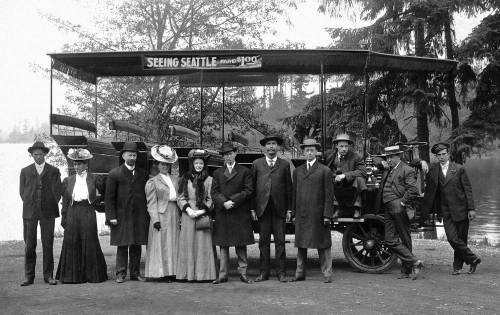 THEN: By 1907 it was possible to bump about Seattle on spring seats visiting its favored attractions for a fee. The ride included both a driver and barker – here the swell fellow in the flattop straw hat arranging his pose in profile second from the right. (Pic courtesy Lawton Gowey)