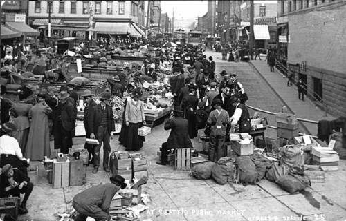 THEN: The Pike Place Market started out in the summer of 1907 as a city-supported place where farmers could sell their produce directly to homemakers.  Since then the Market culture has developed many more attractions including crafts, performers, restaurants, and the human delights that are only delivered by milling and moving crowds.   {Photo Courtesy Old Seattle Paperworks in the Pike Place Market, lower level.)