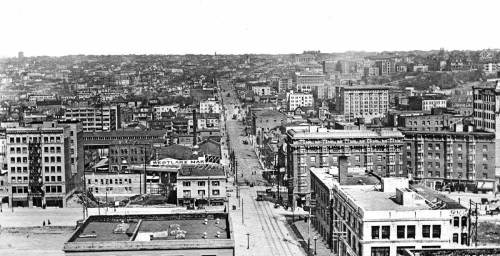 Looking east at the same neighborhood, but from the then new Standard Furniture store at the Northwest corner of 2nd and Pike (now the Gap). The seven-stroy Ritz Hotel, on the left is the prospect from which the neighborhood photograph use above was recorded about two years earlier. Here Pine Street leads east (up) into the center of the view.