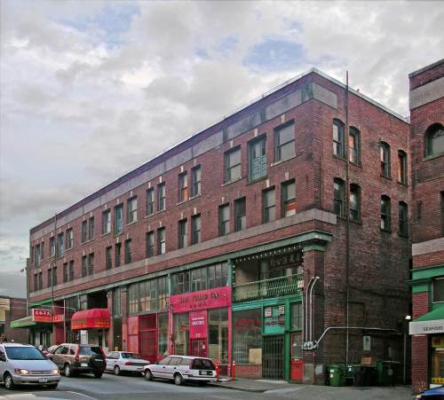 "This ""repeat"" of the East Kong Yick building was photographed in the late autumn of 2005 before the Wing Lunk Asian Museum had moved in.  Aside from the fourth floor balcony overlooking King Street and a change in the building's cornice, at first inspection not uch has changed in the Kong Yick building at the southwest corner of 8th S. and King Street since the Webster and Stevens photography firm took the historical photo ca. 1918."