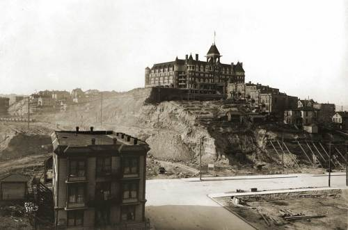 Here the Second Avenue regrade is still underway, and the old Washington Hotel (first named the Denny Hotel) is still in place on top of the souther summit of Denny Hill where it would have stradled Third Avenue could it have climbed the hill.   The south facade of the Blanchard Apartments are apparent on the far left.  The structure bottom-left appears frequently in our recent posting (last week actually) showing Second Avenue south from Pine Street.