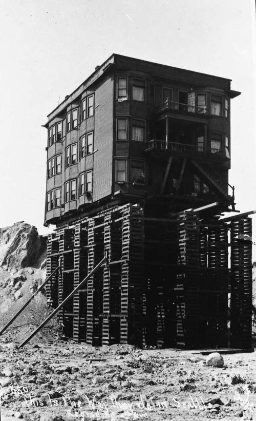 "Lowering the Blanchard Apartments.   I have temporarily lost a negative of the Blanchard resting on top of its ""spike,"" the name for the mounds that were left temporarily by the regraders as their canons attacked the hill from its streets.   I'll put it up went I find it."