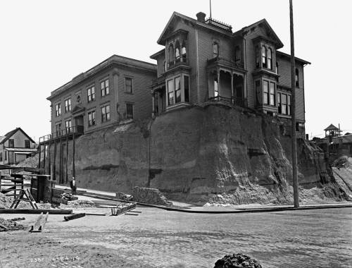 THEN: The city's regrading forces reached Sixth Avenue and Marion Street in 1914. A municipal photographer recorded this view on June 24. Soon after, the two structures left high here were lowered to the street. (Courtesy, Seattle Municipal Archives)