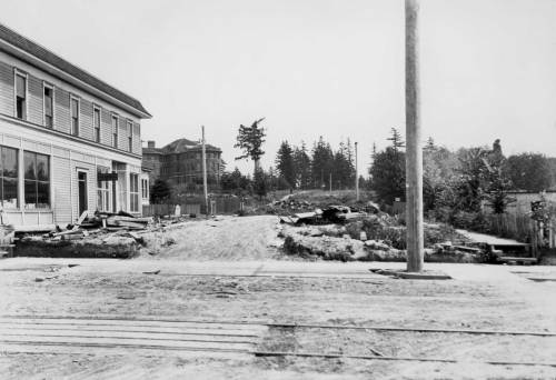 "Looking east across University Way on N.E. 41st Street in 1903 to a nearly new Science Hall (Parrington Hall) left-of-center, on campus. The frame building on the left was razed in memory, I mean I remember it from the late 60s as the home of a guitar shop, and not a chain but a storefront for a skilled guitar ""doctor.""  This is an Olmsted photo done by the firm for their visit here to design the city's park system - and much else."