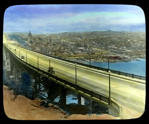 This record of the new Aurora Bridge - with the wrought iron (really wood painted flat black) tower beyond - it is a treat. The rare lantern slide looks north from Queen Anne Hill over the nearly new Aurora Bridge to the north side neighborhoods of Edgewater on the left and Wallingford on the right. The building holding to the horizon on the right is the Good Shepherd Center. The short-lived de l'Edgewater Eiffel la Tour can be seen just breaking the horizon on the left. At some point this lantern slide was hand-colored, as was often the custom, but not with care. The blue area below the bridge while meant to depict the ship canal is actually still south of that waterway's south shore. It should have been given an earth color. Otherwise we have been assured by our private donor that no retouching has been done to the antiquarian lantern slide. Fremont is out of frame to the left. Did you know that the Edgewater Eiffel Tour was built to one-tenth size of the original in Paris? It reached more than 106 feet high! By comparison this made it only ten feet shorter than the Sixth and Pine Building at Sixth and Pine. It was intended that from the top of la Tour Edgewater Eiffel you could see something in all directions including Ballard to the west in spite of Fremont being in the way.