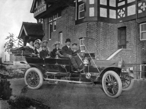 The Hainsworth family motorcar posing with the family and their home on Olga.