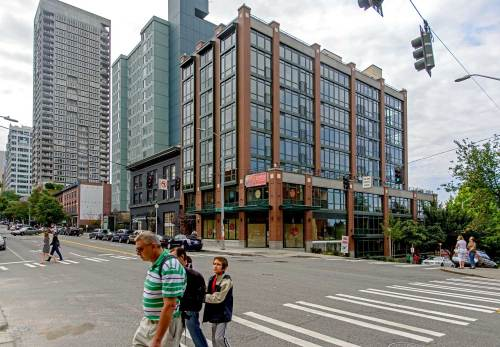 "NOW: In 1910 Hotel Grace took the place of the attached storefronts furthest to the south (on the left) on the ""Rowe Block.""  Soon renamed the Apex Hotel it served the single men who required ""cheap digs"" in the often-depressed Belltown neighborhood.  Later the vacant hotel's two top floors were made over into a ""limited-equity housing coop"" named the Apex Belltown Co-op, which first opened in 1984 with the author one of its first residents.  Rowe's two frame buildings nearest the corner – and at it - were still in service well in the nineteen teens.  They were replaced with a vacant lot, until the recent addition, front-center in Jean's repeat."