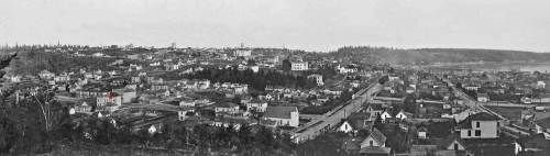 A ca. 1885 pan of the city from Denny Hill, with the Ranke home indicated with a red dot on the left.  A detail of its place near the northwest corner of 5th Ave. and Pike Street is printed below the pan, and a detail from the 1888 Sanborn Real Estate map below it.  The enlarged home is fenced in red.