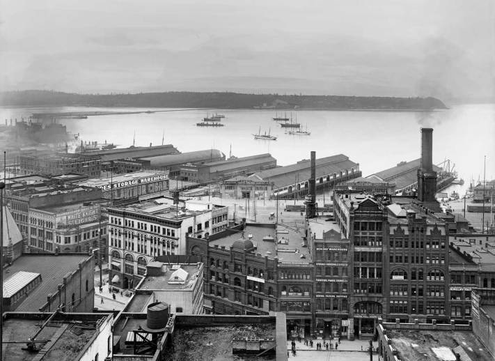THEN: Between the now lost tower of the Pioneer Building, seen in part far left, and the Seattle Electric Steam Plant tower on the right, are arranged on First and Railroad Avenues the elaborate buzz of business beside and near Seattle's Pioneer Square ca. 1904.