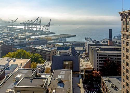 NOW: Both views were recorded from the roof of the Alaska Building at the southeast corner of First Ave. and Cherry Street. In the about 109 intervening years most of the Seattle waterfront here of long finger piers has been flattened and fitted with cranes for containers and more room for the ferries.