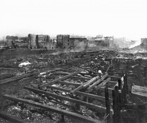 Yesler Wharf ruins from the Great 1889 fire.  Scene looks east from the end of the dock to Pioneer Square and the stately ruins on Front Street (aka First Ave.)