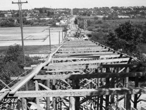 "Construction of the 45th Street Viaduct between the ""upper"" University District and the U.W. Campus and the many plant nurseries fated for the development of University Village.  The Municipal Archive subject dates from 1939 and so too early to find in the distance any traced yet of the Union Bay Village, although its triangle has been cleared, top-right."