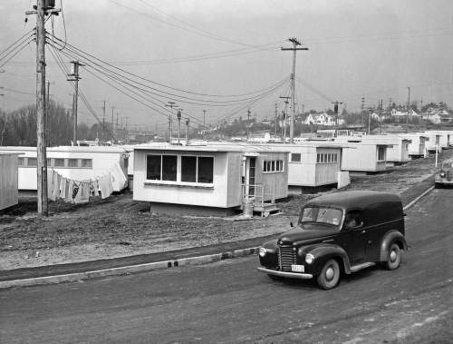 "THEN: On March 25, 1946, or near it, Wide World Photos recorded here what they titled ""University Vet Housing.""   It would soon be named the Union Bay Village and house the families of returning veterans.  The first 45 bungalows shown here rented for from $35 to $45 dollars a month.  It would increase to a ""teeming conglomerate of 500 rental units.""  With housing for both married students and faculty. The view looks north over a street that no longer exists.  The homes on the right horizon face the Burke Gilman Recreation Trail on N.E. Blakeley Street near N.E. 45th Place.  (Courtesy Ron Edge)"