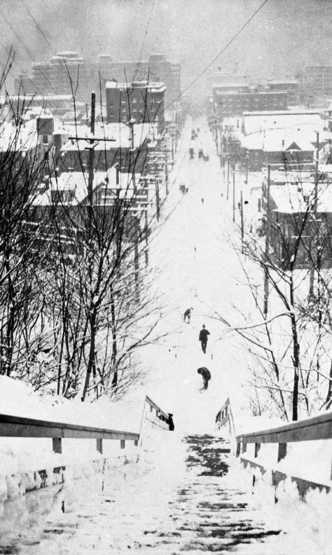 "With her or his  back to Terry Avenue, the photographer looks west on Union Street during the ""Big Snow"" of 1916.  Note the switch-back path."
