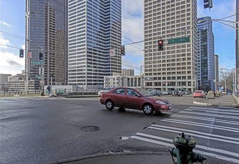 NOW: Aside from the Dover Apartments at 901 6th Avenue, that can be found above the trunk of the red sedan in the foreground, the skyline from the Seattle Tower on the left, to The Renaissance on the right, is new with high-rises that reach far above the frame of Jean's repeat.