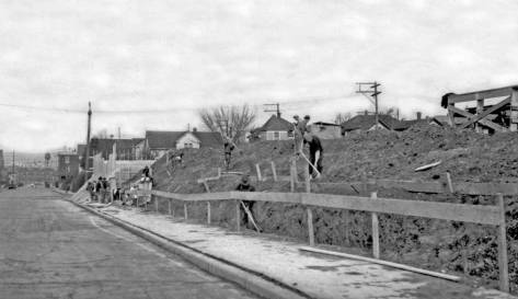 Building a retraining wall along the western border of the Cascade Playfield, depression-time work by the WPA in the 1930.  The view looks north on MINOR AVE. with Thomas Street behind the municipal photographer.