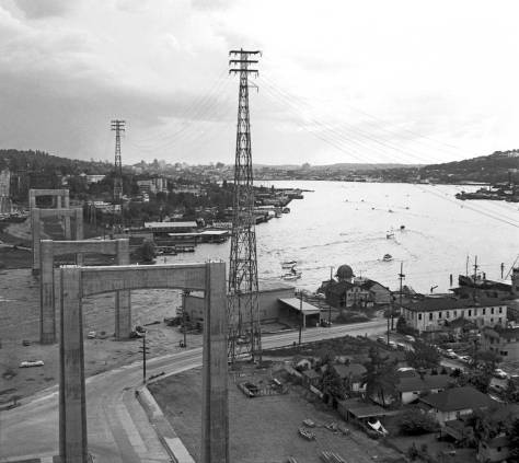 THEN: Long-time Wallingford resident Victor Lygdman looks south through the work-in-progress on the Lake Washington Ship Canal Bridge during the summer of 1959.  Bottom-right are the remnants of the Latona business and industrial district, including the Wayland Mill and the Northlake Apartments, replaced now with Ivar's Salmon House and its parking. (Photo by Victor Lygdman)