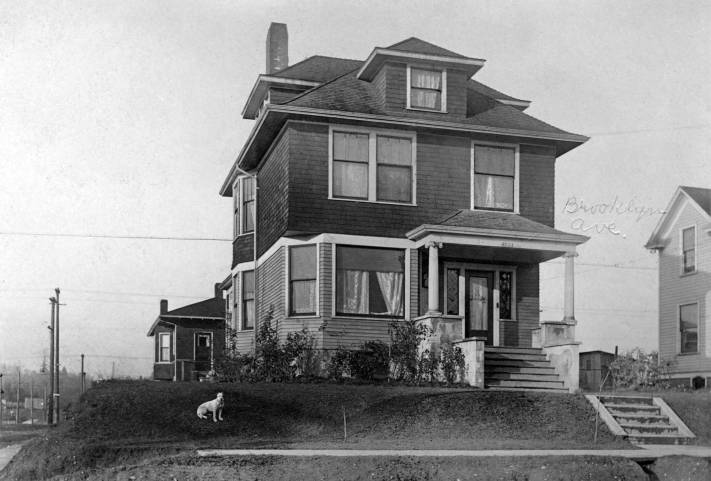 THEN: When it was built in 1902, this box home, with classic Ionic pillars at the porch, was set above the northwest corner of the freshly graded Brooklyn Avenue and 47th Street in the University District. (Courtesy, John Cooper)