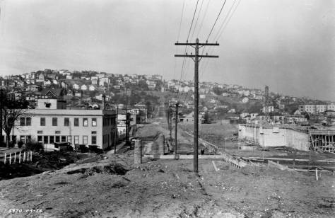 Years later, looking north on 3rd Ave. N. from its southeast corner with Harrison Street, and showing the commercial box, again, far left, at the northwest corner of 3rd and Republican.  The public works photo was recorded on Jan. 9, 1928 as early evidence of work on the new Civic Auditorium.  Some of the same homes on the north side of Mercer Street, included in the subject above this one, appear here as well.  (Courtesy, Municipal Archives.)