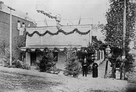Months after the lynching Henry and Sara Yesler pose in front of the home at the northeast corner of Front (First Ave.) and James Street on July 4, 1883.  The hanging trees are on the right.