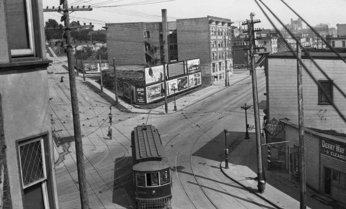 "THEN: In 1913, or near to it, an unnamed photographer recorded this view southeast across the Lower Queen Anne corner of Denny Way and First Avenue North. Out of frame to the left, the northeast corner of this intersection was home then for the Burdett greenhouse and gardens. By its own claim, it offered plants of all sorts, ""the largest and most complete stock to choose from in the state."" Courtesy, the Museum of North Idaho."