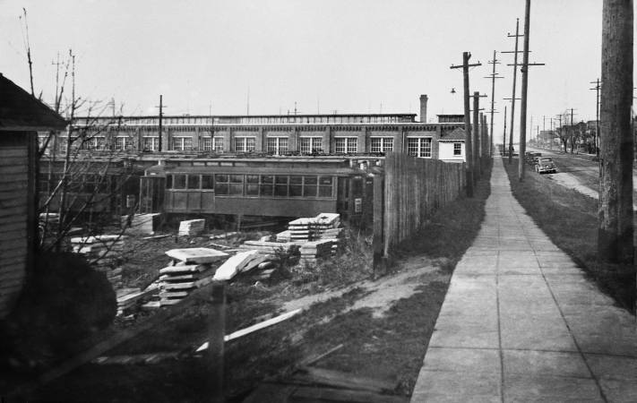 THEN: One of a few photographs recording from different prospects the Fremont trolley car barn on Dec.11, 1936. North 35th Street, on the right, was originally named Blewett for Edward and Carrie Blewett. In 1888 the couple, fresh from Fremont, Nebraska, first named and promoted Fremont as a Seattle neighborhood. That year Fremont also got its lumber mill. (Courtesy, Lawton Gowey)