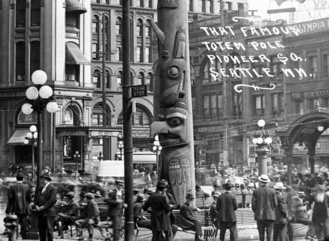 Shall we add the Pioneer Square's stolen totem pole eventually replace the flag pole.  Here the slim front face of the Seattle Hotel, and its cafe, show to the left of the surely famous and infamous totem.
