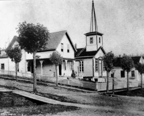 """Seattle's first church the """"White Church"""" and the Methodist Episcopalian parish home to this side of it on the southeast corner of Second Avenue and Columbia in the 1870s."""