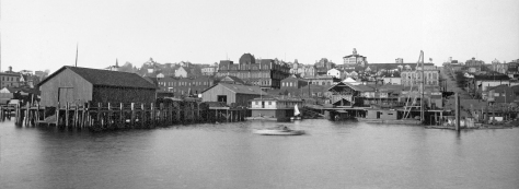 The waterfront ca. 1884 with an early Colman Dock on the left, Columbia Street on the right, and a short feature essay below the contemporary repeat photographed officially - only - in the anxious glow of 911 by Shawn Devine, and employee of the Washington State Ferries.