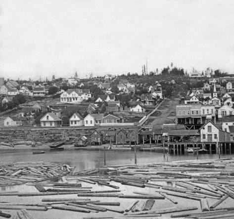 """A Peterson and Bros. photograph taken from the end of a dog-legged Yesler Wharf and looking up Columbia Street on the right in 1878.  Note the tower for the """"White Church"""" on the right, the Methodist Episcopalian congregation that was the first in Seattle.  It sits there at the second lot south of Columbia on the east side of Second Avenue.  Also note that for the most part First Hill has been denuded of the virgin forest that still covered this skyline as late as 1872."""