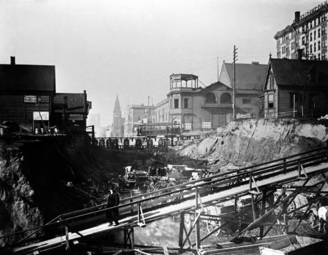 Third Ave. Regrade 1906, looking north over Marion Street.  The Third Ave. Theatre, its tower half-decapitated, stands on the far side of the Madison Street Cable Railway trestle.  The upper-right corner shows the west facade of the Lincoln Hotel at the northwest corner of 4th Ave. and Madison Street.