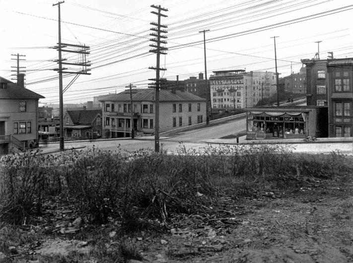 THEN: Looking north-northeast from a low knoll at the southwest corner of Seneca Street and Seventh Avenue, circa 1916. By 1925, a commercial automobile garage filled the vacant lot in the foreground. [Courtesy, Ron Edge]