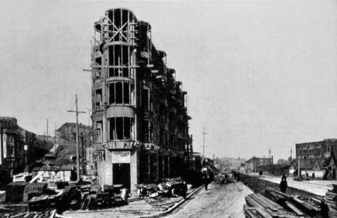 The Plaza Hotel underconstruction during the 1906 paving of the then brank new Westlake.  The view looks north from 4th and Pike.  On the left, Fourth Avenue still climbs Denny Hill.