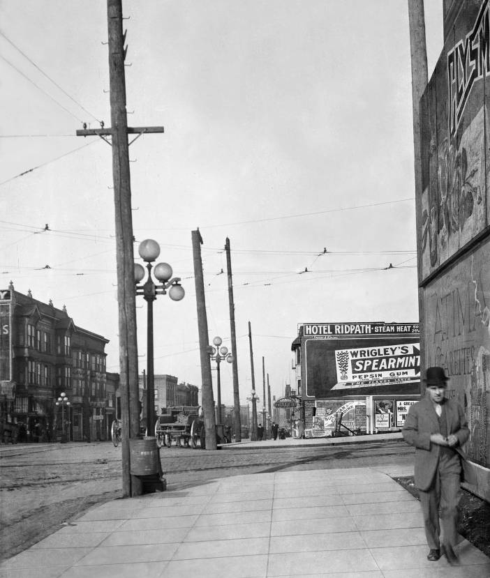 "THEN: In 1910, a circa date for this look north on First Avenue across Virginia Street, the two corners on the east side of the intersection were still undeveloped – except for signs. The Terminal Sales Building, seen far right in Jean Sherrard's repeat, did not replace the billboards that crowd the sidewalk in the ""then"" until 1923. (Seattle Municipal Archive)"