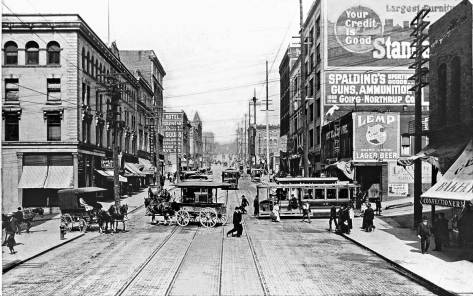 Looking north on First thru Madison Street with a cable car intersecting on the right.  Note the sidewalk awning of the German Bakery, far right.  The Globe Building is on the left at the northwest corner.