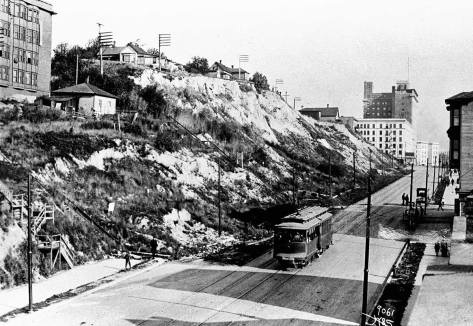 The cliff along the east side of Second Avenue, looking south from near Bell Street.  The Moore Theatre and beyond it the New Washington Hotel are evident beyond Virginia Street.