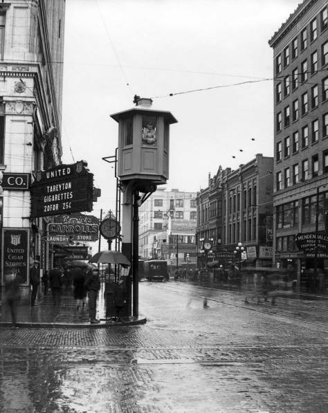 "THEN: Looking west on Pike Street from Fourth Avenue, the variety in the first block of this retail district includes the Rhodes Bros. Ten Cent Store, Mendenhall's Kodaks, Fountain Pens and Photo Supplies, Remick's Song and Gift Shop, the Lotus Confectionary, Fahey-Brockman's Clothiers, where, one may ""buy upstairs and save $10.00"".  (Courtesy, MOHAI)"