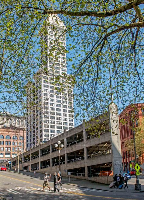 "NOW:  The mockingly named ""Sinking Ship Garage"" replaced the ornate brick Seattle Hotel with a concrete garage capped by a railing of bent pipes that resemble a row of basket handles."