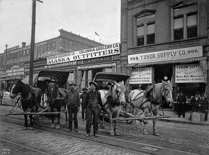 THEN: During the few years of the Klondike Gold Rush, the streets of Seattle's business district were crowded with outfitters selling well-packed foods and gear to thousands of traveling men heading north to strike it rich – they imagined. (Courtesy, Museum of History and Industry)