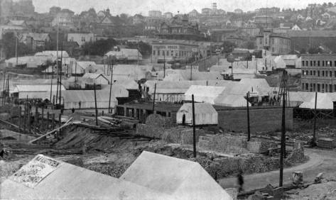 Some of the same tents and brick piles show in this view that looks northeast across Main Street to Second Ave. (Occidental Ave.).  The County Courthouse at Third and Yesler appears on the right and the Yesler Mansion on the east side of Third, high-center.  Part of Central School at Madison and 6th Ave. , fills the upper-left corner.  (Courtesy, MOHAI)