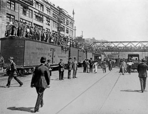 "THEN: From boxcars and rooftops to the planks of Railroad Avenue, excitement builds for the ceremonial re-enactment of the S.S.Portland's 1897 landing with its ""ton of gold"" on the Seattle waterfront, the city's first Golden Potlatch Celebration.  [Courtesy, Michael Maslan]"