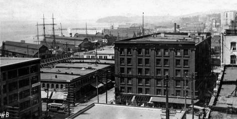 Looking northwest and down on the intersection of Western Ave. and Madison Street from the nearly new Rainier Grand hotel on First  Avenue.  Note the Madison Street Cable Car approaching the intersection.  Beyond the tall ships, a trestle for moving the mud of Denny Hill reaches into the bay.   The new Maritime Buildings northeast corner appears far left.