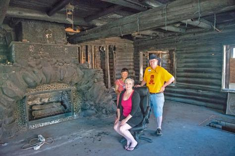 NOW: Southwest Seattle Historical Society supporters Annie Tigtig and Kippy Jo Alexander (seated) pose with director Clay Eals for Jean Sherrard beside the charred Homestead's fireplace. One of the mysteries of Fir Lodge/Alki Homestead is why the original fireplace was enlarged with the rock crown added in the mid-1930s. One of the puzzles of landmark preservation, and for the new owner-restorer, is should the living room hearth be returned to its former glory or be kept with this dark rock corona?