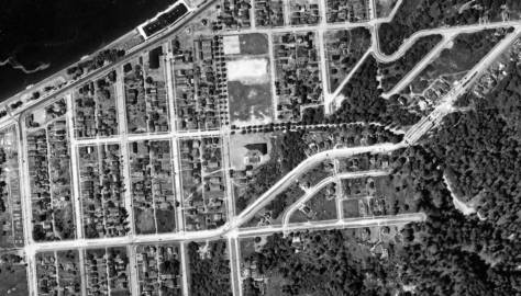 Even the beach shack that was home to the first SPUD cam be found in this detail from the 1936 aerial. It appears directly across Alki Avenue from the bath house that appears here right-of-center.