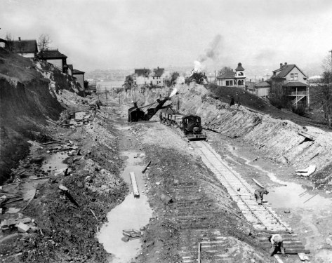 Looking north on 9th Avenue with the photographer's back to Denny Way. The regraded cliff to Denny Park's eastern border is on the left. The Gas Tanks are hidden behind the homes upper-left.