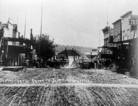 The opposite direction, looking south on Front through its intersection with Cherry Street, with the front facade of the box-shaped two story commercial building holding the Kellog Drug store centered on the south side of Mill Street (Yesler Way). Note that the scrawl on the mud of Front Street just above the worn foot crossing on Cherry, dates this scene 1878. [Courtesy, Seattle Public Library]
